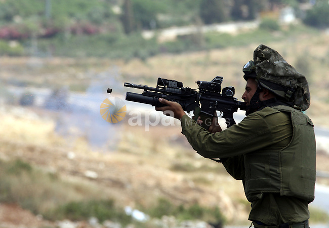 An Israeli soldier fires tear gas canister during clashes with Palestinian protestors in the West  Bank village of Nabi Saleh, on 28 May 2010. Palestinians protest weekly against the neighbouring Jewish settlement of Halamish. photo by Eyad Jadallah