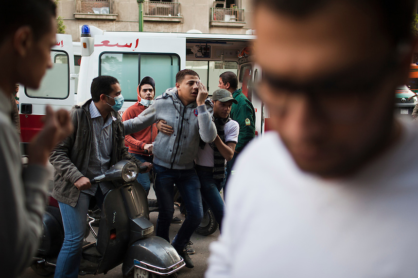 An injured Egyptian protester arrives at a field hospital after being ferried by motorbike from clashes in Cairo's Tahrir Square, November 21, 2011.  Photo: Ed Giles.