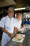 "Kenichi and Etsuko Yasuda, president and manager of Harumiya Co., prepare food for guests arriving for an evening aboard one of the family-run company's ""yakata-bune"" pleasure boats in Tokyo, Japan on 31 August  2010. Photographer: Robert Gilhooly"