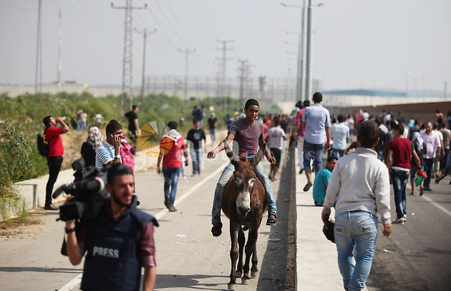 A Palestinian boy rides on a donkey during clashes with Israeli security forces next to the border fence with Israel, at the Erez crossing in the northern Gaza strip, on October 13, 2015. A wave of stabbings that hit Israel, Jerusalem and the West Bank this month along with violent protests in annexed east Jerusalem and the occupied West Bank, has led to warnings that a full-scale Palestinian uprising, or third intifada, could erupt. The unrest has also spread to the Gaza Strip, with clashes along the border in recent days leaving nine Palestinians dead from Israeli fire. Photo by Ashraf Amra
