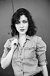 Dark curly hair, woman in black and white wearing denim shirt