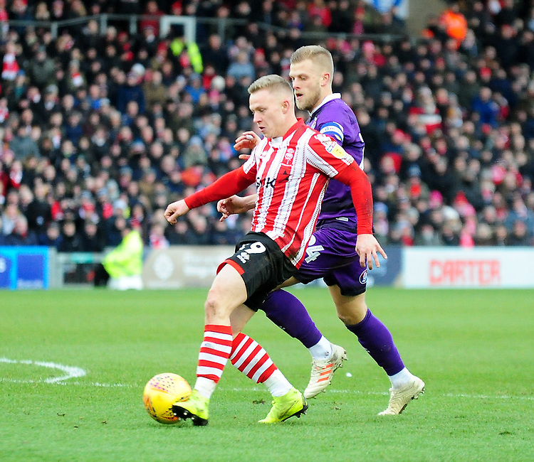 Lincoln City's Danny Rowe under pressure from Grimsby Town's Harry Davis<br /> <br /> Photographer Andrew Vaughan/CameraSport<br /> <br /> The EFL Sky Bet League Two - Lincoln City v Grimsby Town - Saturday 19 January 2019 - Sincil Bank - Lincoln<br /> <br /> World Copyright &copy; 2019 CameraSport. All rights reserved. 43 Linden Ave. Countesthorpe. Leicester. England. LE8 5PG - Tel: +44 (0) 116 277 4147 - admin@camerasport.com - www.camerasport.com