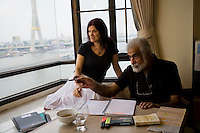 "Eli Evioni and Dina Evioni look out to the Chao Phraya river (with the Rama 9 bridge in the background) from the window of their one-bedroom apartment near Khao San Chabad in Bangkok, Thailand, on 13th December 2009. Eli is writing a book on his life...Eil: Aged 68; Born in Israel to parents from Yemen; grew up and joined the army, been through the wars of '56 and '67 where he first met people from Chabad who came to put tefillin and bring donuts even in the desert camps. Eli remembered seeing soldiers putting tefillin on tanks in '67 when 2 planes flew from the egyptian side. He thought that it was an attack but suddenly, the planes flipped, a sign of victory over the enemy. Left Israel to complete studies in England where he met his wife, Dina. Eli has worked in a musica theater for many years, and then became a jewellery designer, folowing family footsteps. After marriage, he travelled with Dina as spouse and stayed at home, building a house and bringing up the kids. Currently, Eli is writing a book about his life. They've been living in Bangkok for 5 years so far. Eli still feels the only home is Israel. ..Dina: Aged 66; Born in England to non-religious parents from East Europe, mostly Russia. Grew up very secular, ""felt like her birthright was stolen from her"". When she met Eli, he brought her back. but it was only when they moved to Thailand and was involved with Chabad that she really felt that Chabad was giving her heritage back. Dina worked and retired from the UN in Geneva. Now, she works as a freelance translator for the UN. ..They chose the flat because of its proximity to Chabad Khao San. They miss chabad khao san terribly whenever abroad. ""Once, I came back from a harsh time in Europe. I saw the face of the rabbi and his wife. their home was fully lit... and i felt like the light of G-d had entered me. I go to the synagogue every shabbat now.. like i never did before in my life. Because of Chabad. They give you love for free..."" says Eli...Photo by Suz"