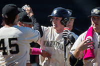 Kevin Conway (center) high fives teammates after scoring a run against the Virginia Tech Hokies at Wake Forest Baseball Park on March 7, 2015 in Winston-Salem, North Carolina.  The Hokies defeated the Demon Deacons 12-7 in game one of a double-header.   (Brian Westerholt/Four Seam Images)