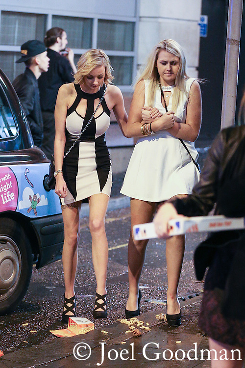 © Joel Goodman - 07973 332324 . No syndication permitted . 01/01/2014 . Manchester , UK . Two women cross by a taxi rank , stepping over fast food debris . Revellers see in the New Year in Manchester today (January 1st 2014) as police report that officers are at full stretch responding to calls . Photo credit : Joel Goodman