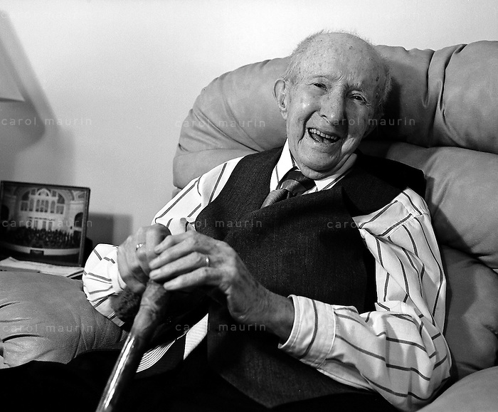 Laughing elderly Caucasian man with cane wearing a tie and vest