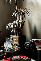 In the corner of the sitting room stands a beautifully eccentric brass palm light by Maison Jansen. The Chesterfield bar trolley is from the early 1950s and the wall paper is by Ulf Moritz.