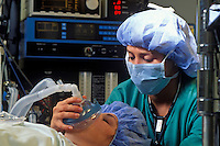 Anesthesiologist moniters a surgical patient.