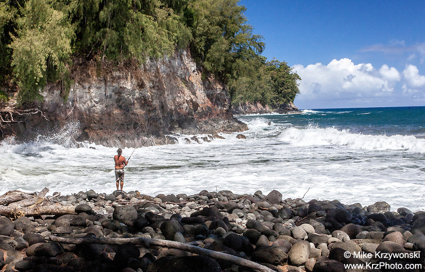 Caucasian man fishing from rocky shoreline at Kolekole Beach Park in Honomu, Big Island, Hawaii