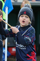 A young flag bearer waits to welcome the players ahead of the Greene King IPA Championship match between London Scottish Football Club and Jersey at Richmond Athletic Ground, Richmond, United Kingdom on 18 February 2017. Photo by David Horn / PRiME Media Images.
