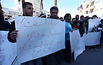 Palestinian vendors hold placards during a protest against the government decision to remove the street vendors in the West Bank city of Ramallah, Feb 03, 2013. Photo by Issam Rimawi