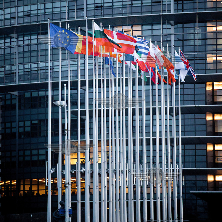 National flags of the member states fly outside the building of the European Parliament.