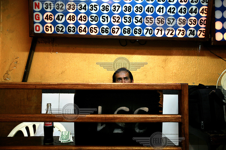 A man plays Bingo in a popular venue in old Quito. Gambling has been banned under the new Ecuadorean constitution and all such venues will eventually have to close down.