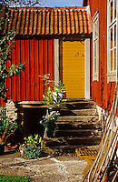 The back door has been painted a bright yellow in contrast to the deep russet clapboard walls