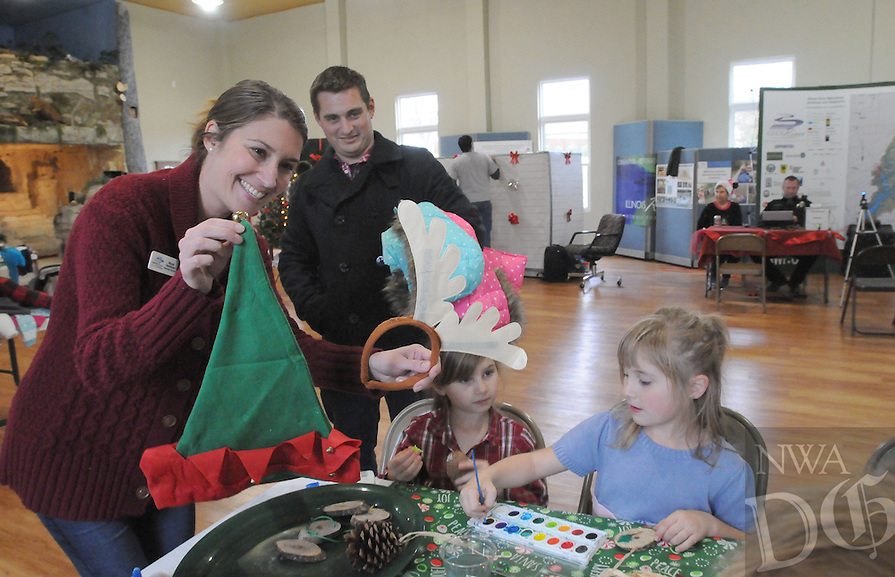 NWA Democrat-Gazette/FLIP PUTTHOFF <br /> CAVE SPRINGS CHRISTMAS<br /> Nicole Hardiman, executive director of the Illionois River Watershed Partnership, hands out Christmas hats and antlers to young craft makers Saturday Dec. 10 2016 at the partnership's learning center in downtown Cave Springs. Aaron Pace of Cave Springs (second from left) watches his daughters (from left) Aurora, 7, and Evangeline, 6, paint pine cones at the craft table. Festivities were part of Christmas in Cave Springs hosted by the city and the Illinois River Watershed Partnership. Activies also included visits with Santa, fingerprint identification for children and nature hikes.