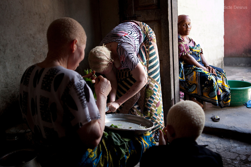 June 28, 2010 - Dar es Salaam, Tanzania - Ali's two ives and his children prepare dinner at home. Ali Mohamed is a 61 year old Muslim man with albinism living in Tanzania where he has a shop selling rice and grains. Ali married his first wife, Jutia Jalehe, in 1978. Jutia is also an albino and together they had 1 son with albinism named Salehe Ally. In 1983, Mohamed married his second wife, Nuru Mohamedy who did not have Albinism. Together they had 6 children, two of them with albinism and four of them without albinism. Albinism is a recessive gene but when two carriers of the gene have a child it has a one in four chance of getting albinism. Tanzania is believed to have Africa' s largest population of albinos, a genetic condition caused by a lack of melanin in the skin, eyes and hair and has an incidence seven times higher than elsewhere in the world. Over the last three years people with albinism have been threatened by an alarming increase in the criminal trade of Albino body parts. At least 53 albinos have been killed since 2007, some as young as six months old. Many more have been attacked with machetes and their limbs stolen while they are still alive. Witch doctors tell their clients that the body parts will bring them luck in love, life and business. The belief that albino body parts have magical powers has driven thousands of Africa's albinos into hiding, fearful of losing their lives and limbs to unscrupulous dealers who can make up to US$75,000 selling a complete dismembered set. The killings have now spread to neighboring countries, like Kenya, Uganda and Burundi and an international market for albino body parts has been rumored to reach as far as West Africa. Photo credit: Benedicte Desrus