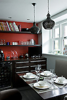 This kitchen/dining area has a red-painted signature wall and a table and kitchen units of iroko wood