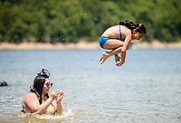NWA Democrat-Gazette/CHARLIE KAIJO (From right) Jazlynn Cortez, 6, leaps from the shoulders of Mel Reyes of Rogers during a warm afternoon, Sunday, July 8, 2018 at the Prairie Creek Marina in Rogers.