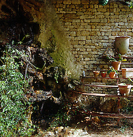 A rusting jardiniere stands against a stone wall inside the restored conservatory beside a grotto with a small waterfall