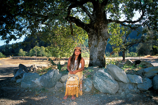 Full shot of a traditional Yurok girl (11yrs old); sits under an old oak tree while dressed in a traditional leather skirt decorated with shells; seeds and woven grass. Jene also is wearing traditional beaded shell necklaces and a basket woven hat. Hoopa California