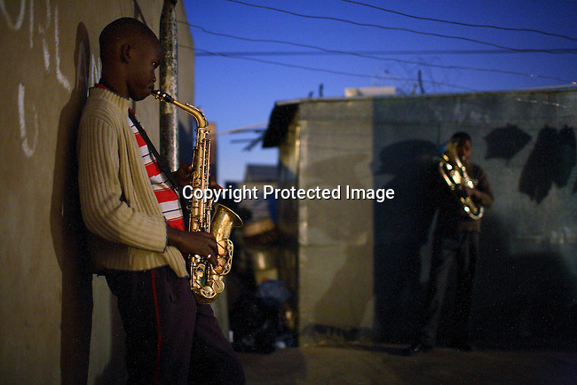 Youth members of a Brass band rehearse in the back yard of a home in Soweto.