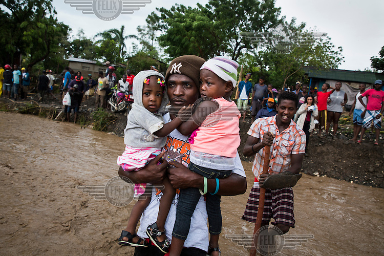 A man carries two young children over La Digue River. Following the collapse, during Hurricane Matthew, of a bridge people were forced to wade across the water course. The downfall of the bridge meant emergency responders where unable to reach the worst hit southwestern peninsula of the island. Hurricane Matthew, the first category 5 Atlantic hurricane since 2007, hit the island on 4 October 2016. Winds of up to 230km/h (145mph) tore across the worst affected areas, mainly in the south of the island, killing around over 1,000 people and leaving hundreds of thousands in need of assistance.
