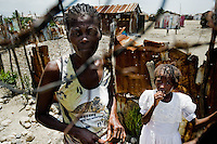 A Haitian woman and her daughter stand behind a wire fence in the slum of Cité Soleil, Port-au-Prince, Haiti, 16 July 2008. Cité Soleil is considered one of the worst slums in the Americas, most of its 300.000 residents live in extreme poverty. Children and single mothers predominate in the population. Social and living conditions in the slum are a human tragedy. There is no running water, no sewers and no electricity. Public services virtually do not exist - there are no stores, no hospitals or schools, no urban infrastructure. In spite of this fact, a rent must be payed even in all shacks made from rusty metal sheets. Infectious diseases are widely spread as garbage disposal does not exist in Cité Soleil. Violence is common, armed gangs operate throughout the slum.