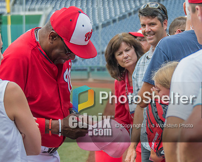 23 July 2016: Washington Nationals Manager Dusty Baker signs a pink cap for a fan prior to a game against the San Diego Padres at Nationals Park in Washington, DC. The Nationals defeated the Padres 3-2 on a Stephen Drew pinch-hit, walk-off triple in the bottom of the 9th inning to tie their series at one game apiece. Mandatory Credit: Ed Wolfstein Photo *** RAW (NEF) Image File Available ***