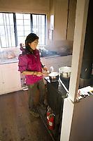 Woman cooking breakfast in a cabin in Haleakala National Park