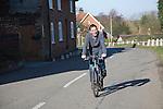 Smiling middle aged man cycling along village road, Shottisham, Suffolk, England
