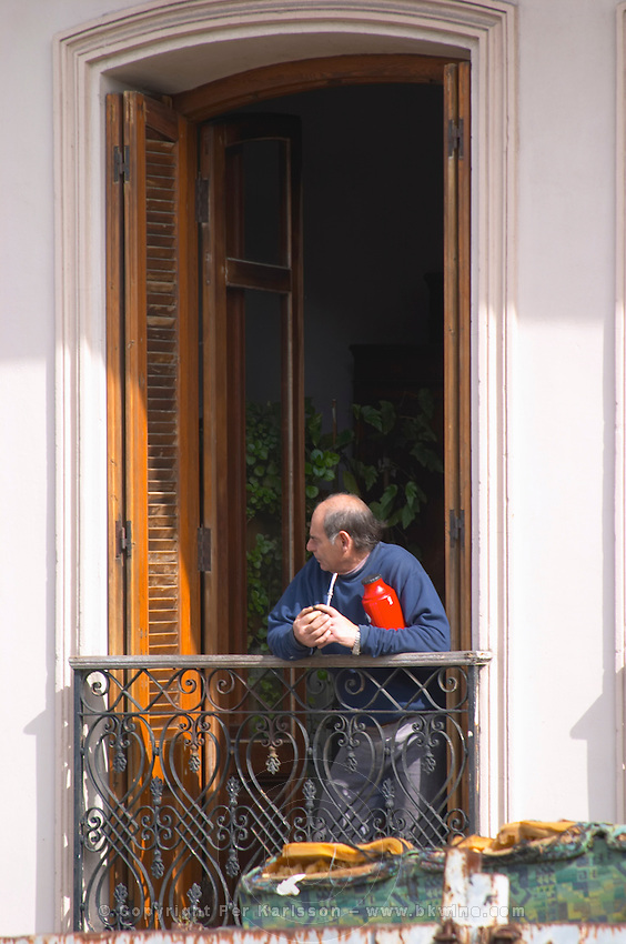 A man standing in a window with a wrought iron railing holding a cup and a hot water flask thermos with mate herbal tea. Montevideo, Uruguay, South America