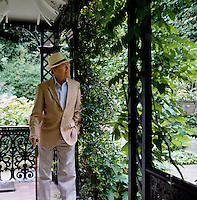 Portrait of Lord Snowdon standing on the covered terrace he designed around his London home