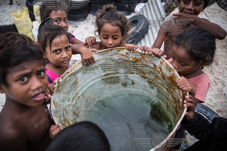 Children from Eita village gather around a barrel filled with rain water.