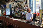 Barman inside Gleneagles Bar pub at Mgarr, Gozo, Malta