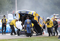 Oct 2, 2016; Mohnton, PA, USA; NHRA safety safari crews tend to funny car driver Ron Capps after an engine fire during the Dodge Nationals at Maple Grove Raceway. Mandatory Credit: Mark J. Rebilas-USA TODAY Sports