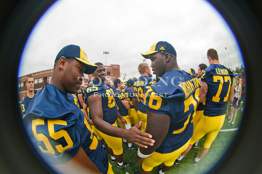 Michigan defensive end Jibreel Black (55), offensive lineman Patrick Omameh (65) and offensive lineman Quinton Washington (76) wait for their pictures to be taken, at the annual NCAA college football media day, Sunday, Aug. 22, 2010, in Ann Arbor, Mich. (AP Photo/Tony Ding)