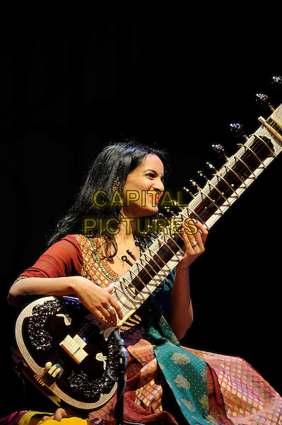 Anoushka Shankar.performing in concert, Queen Elizabeth Hall, Waterloo, London, England, UK, 13th April 2013..music live on stage performing gig half length sitting indian dress sari costume orange red gold embroidered patterned green silk  playing sitar instrument traditional Indian classical bare foot feet .CAP/MAR.© Martin Harris/Capital Pictures.