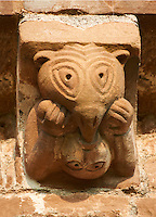Norman Romanesque exterior corbel no 35  -  sculpture of.a curious scene. A beaked headed creature holds down a man below its body and is pushing its beak into the mans mouth, The beaked creature seems to be holding something in its right hand which it is eating The Norman Romanesque Church of St Mary and St David, Kilpeck Herefordshire, England. Built around 1140