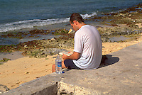 Man age 30 on rock reading at the ocean side in Mexico.  Cozumel   Mexico