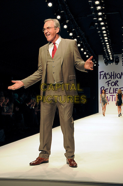 LARRY LAMB.The Fashion For Relief Haiti 2010 show for London Fashion Week Autumn/Winter 2010 at Somerset House, London, England..February 18th, 2010.LFW catwalk runway full length beige suit brown waistcoat glasses hands.CAP/CAS.©Bob Cass/Capital Pictures.