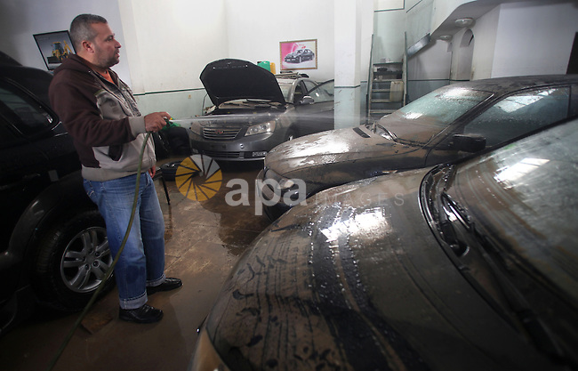 A Palestinian man cleans his cars at car showroom in Gaza City, Dec. 21, 2013. Rescue workers evacuated thousands of Gaza Strip residents from homes flooded by heavy rain, using fishing boats and heavy construction equipment to pluck some of those trapped from upper floors. Photo by Yasser Qudih