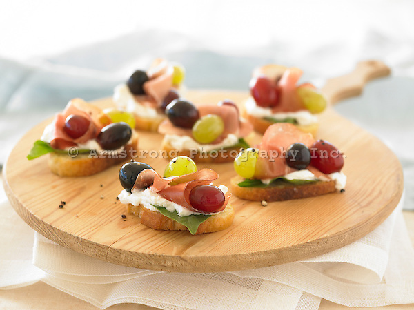 Bruschetta - slices of baguette with cheese, prosciutto, and grapes