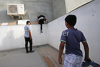 Photographer: Rick Findler..21.04.13 Young protesters flee from one house to another as police search properties after clashes between the two this afternoon in Bahrain, as the Bahrain Grand Prix gets underway. The number of protests in Bahrain increase dramatically during the sporting event to help bring attention to the ruling bahraini Sunni royal family's many human rights abuses and repression of the country's Shiite people.