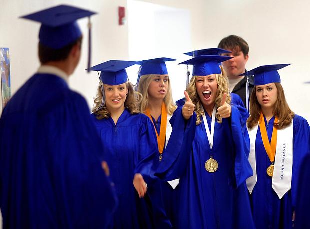 Ankeny Christian Academy graduating senior Jennifer Maertens of Ankeny, second from right, signals thumbs up to classmate Loren Carroll of Pleasant Hill, far left, while walking to Commencement with the rest of Ankeny Christian's class of 2006 Saturday, May 20, 2006.  Ankeny Christian graduated a class of seven.