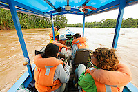 Tourists on boat running up Tambopata River, Peru