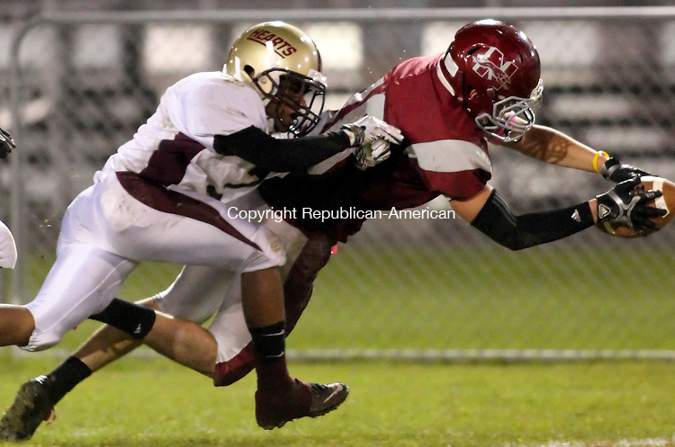 Naugatuck, CT- 07, October 2011-100711CM11  Naugatuck's Besim Bomova dives in the end zone for a touchdown in the first quarter, as Sacred Heart Shyquan Thompson tries to make the tackle in Friday night in Naugatuck.  Naugy won 34-29.   Christopher Massa Republican-American