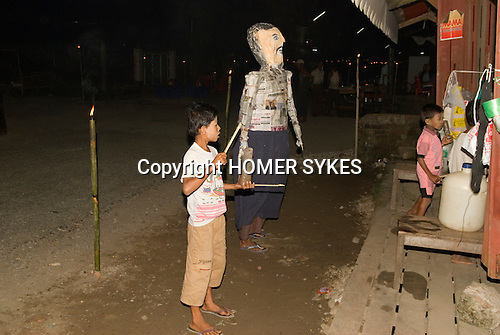 Sittwe Northern Rakhaing province Myanmar (Burma) 2008. Full Moon festival. Children paarade comical figure through the streets collecting money from residents.