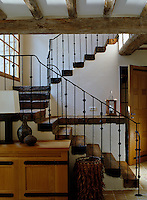 The staircase is constructed of local oak with a forged iron balustrade handcrafted in England