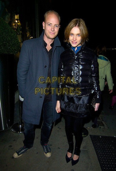JUSTIN PORTMAN & NATALIA VODIANOVA.Kova & T clothing range launch party, Harvey Nicholls, London, England..November 22nd, 2007.nichols full length black puffer jacket coat jeans denim blue coat married husband wife skirt.CAP/CAN.©Can Nguyen/Capital Pictures