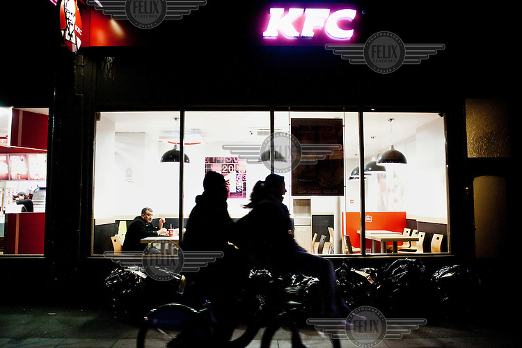 A man eating at KFC watches a couple on a bike, central London.